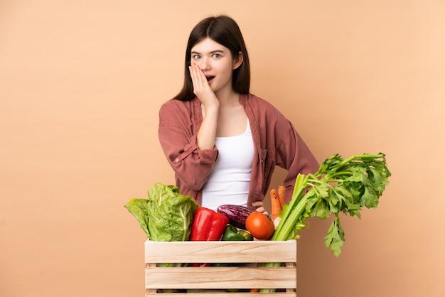 Garota jovem agricultor com legumes recém colhidos em uma caixa surpreso e chocado ao olhar certo