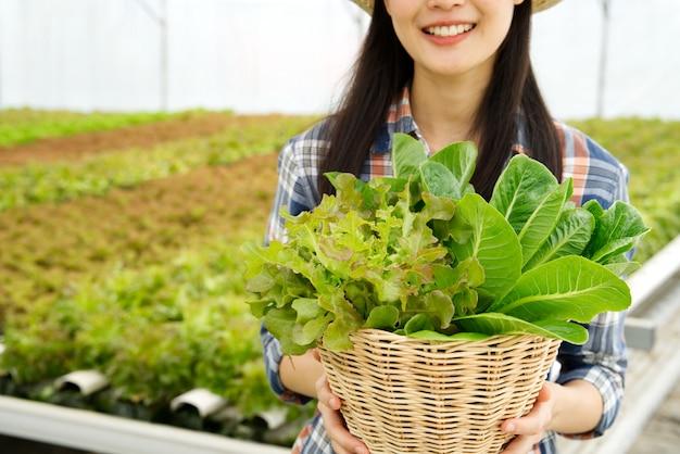 Garota jovem agricultor segurando cesta de legumes na fazenda hidropônica com sorriso