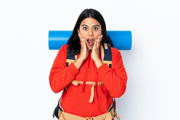 Garota jovem alpinista colombiana com uma mochila grande isolada no branco