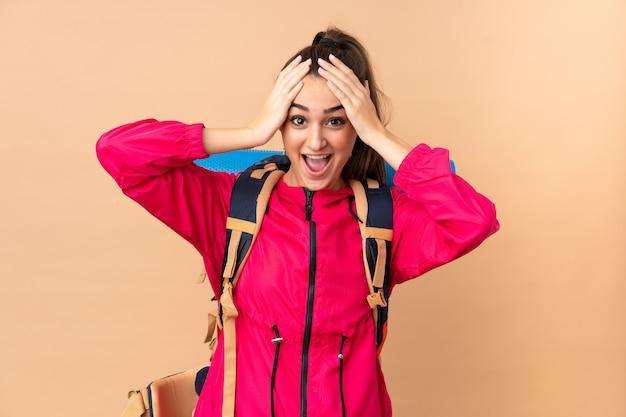 Garota jovem alpinista com um grande mochileiro isolado no bege com expressão facial de surpresa