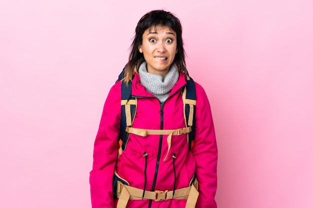 Garota jovem alpinista com uma mochila grande muro rosa tendo dúvidas e com a expressão do rosto confuso