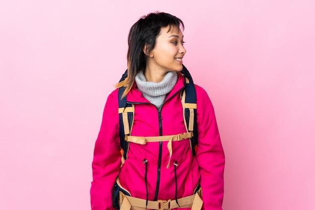 Garota jovem alpinista com uma mochila grande no isolado rosa olhando para o lado
