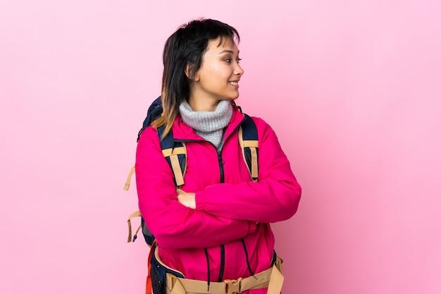 Garota jovem alpinista com uma mochila grande parede rosa, olhando para o lado