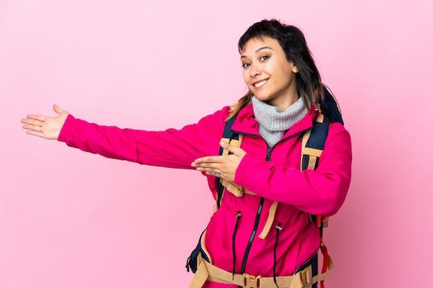 Garota jovem alpinista com uma mochila grande sobre parede rosa, estendendo as mãos para o lado