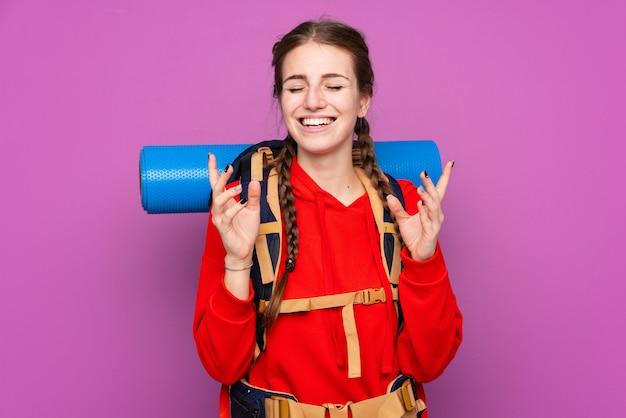 Garota jovem alpinista com uma mochila grande sobre parede roxa isolada rindo