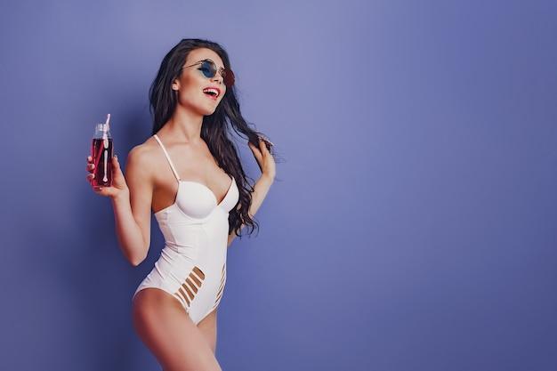 Garota jovem animada em maiô branco de uma peça, óculos de sol posando com bebida isolada no fundo roxo.