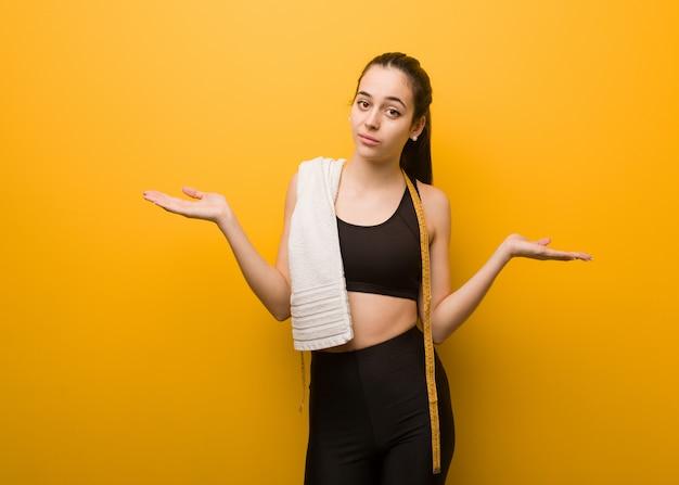 Garota jovem aptidão duvidando e encolher os ombros