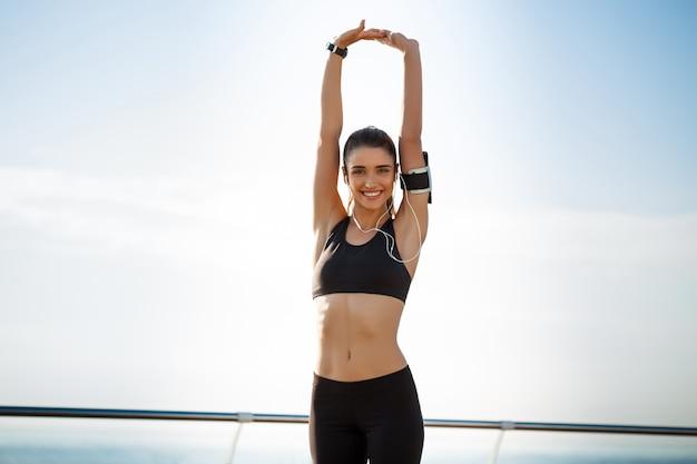 Garota jovem aptidão pronta para exercícios de esporte à beira-mar