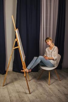 Garota jovem artista em uma camisa branca e calça jeans azul, pinta uma imagem sobre tela na oficina. um jovem estudante usa pincéis, telas e cavaletes. trabalho criativo para crianças e adultos.