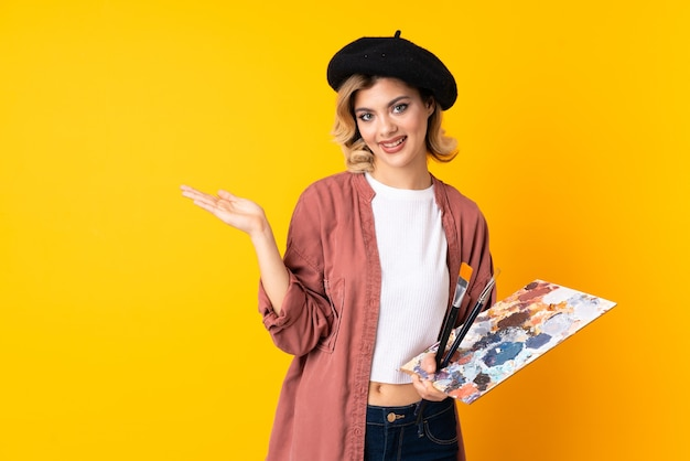 Garota jovem artista segurando uma paleta isolada na parede amarela segurando copyspace imaginário na palma da mão