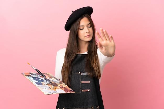Garota jovem artista segurando uma paleta sobre um fundo rosa isolado, fazendo um gesto de pare e desapontada