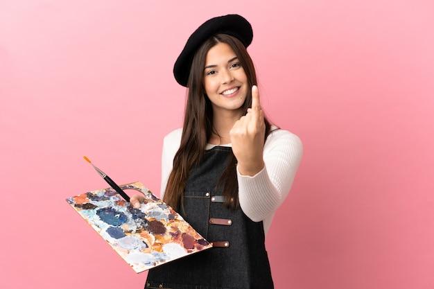 Garota jovem artista segurando uma paleta sobre um fundo rosa isolado fazendo um gesto próximo