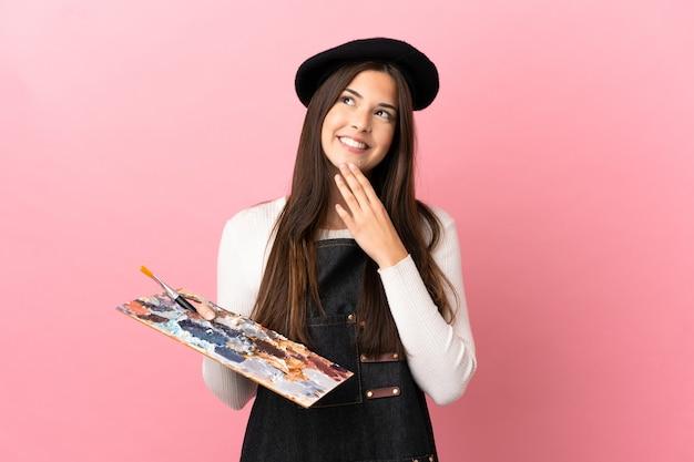 Garota jovem artista segurando uma paleta sobre um fundo rosa isolado, olhando para cima enquanto sorri