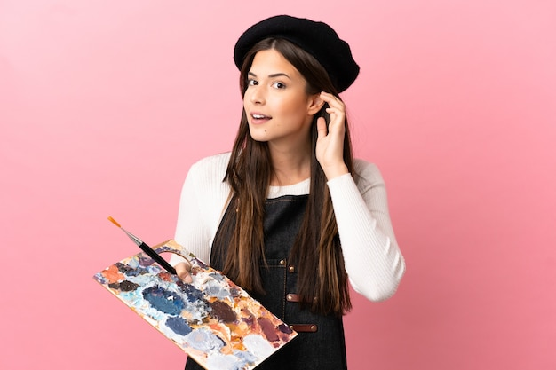Garota jovem artista segurando uma paleta sobre um fundo rosa isolado, ouvindo algo colocando a mão na orelha