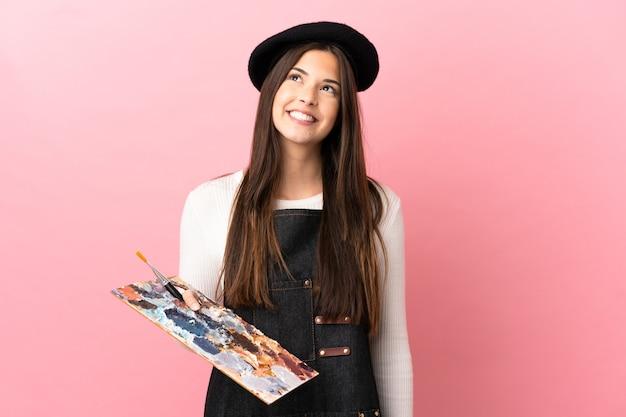 Garota jovem artista segurando uma paleta sobre um fundo rosa isolado pensando em uma ideia enquanto olha para cima