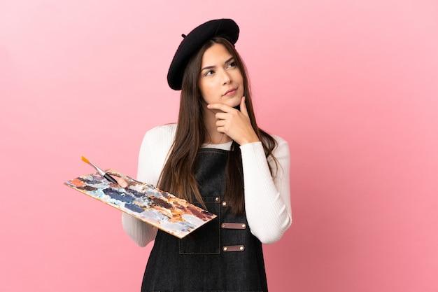 Garota jovem artista segurando uma paleta sobre um fundo rosa isolado, tendo dúvidas