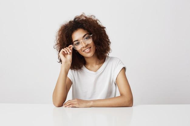 Garota jovem atraente designer de moda africana em copos sorrindo sentado à mesa sobre parede branca