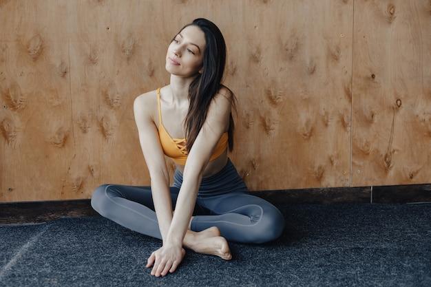 Garota jovem atraente fitness sentado no chão