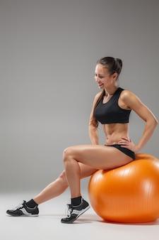Garota jovem, bonita, esportes, fazendo exercícios em uma fitball