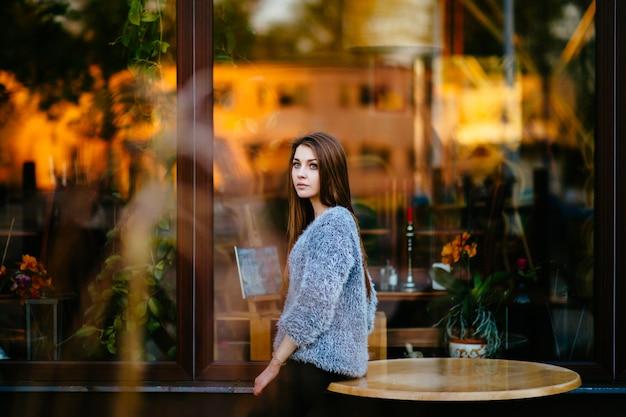 Garota jovem bonita modelo estranho com rosto pensativo sensual posando para a câmera ao ar livre na frente da vitrine de loja com reflexões abstratas na manhã. incrível fêmea adolescente com olhos azuis humor retrato