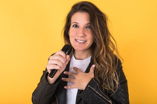 Garota jovem cantora vestindo jaqueta de couro preta cantando com microfone amarelo.