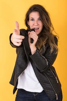 Garota jovem cantora, vestindo jaqueta de couro preta, cantando com microfone e apontando com a mão em amarelo.