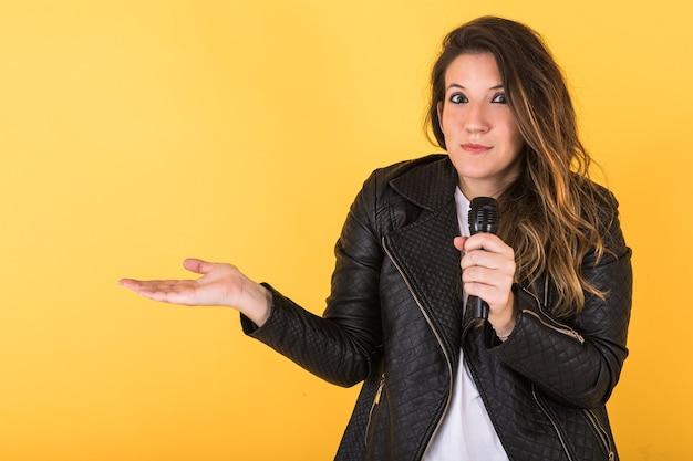 Garota jovem cantora, vestindo jaqueta de couro preta e microfone, fazendo gesto de descrença em amarelo.
