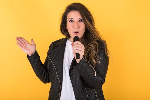 Garota jovem cantora, vestindo jaqueta de couro preta e microfone, fazendo gesto surpresa em amarelo.