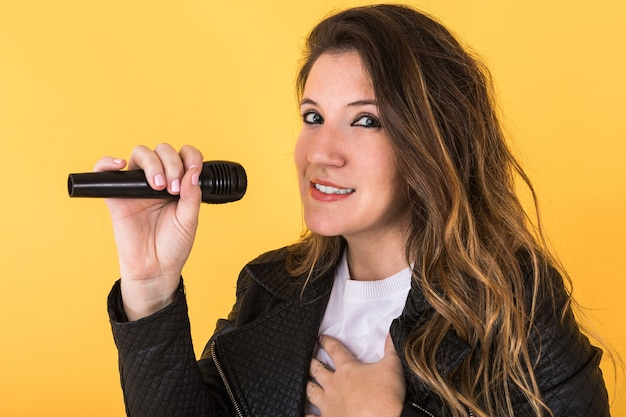 Garota jovem cantora vestindo jaqueta de couro preta, olhando para a câmera com microfone amarelo.