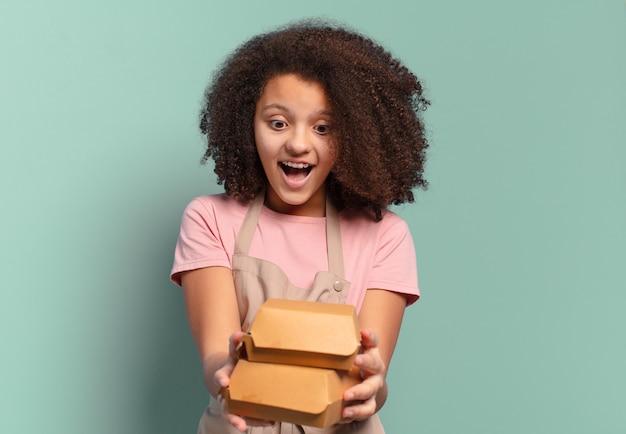Garota jovem chef afro com caixas de hambúrgueres para viagem