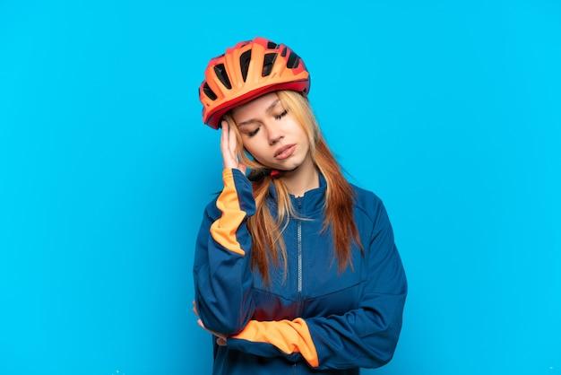 Garota jovem ciclista isolada em um fundo azul com dor de cabeça