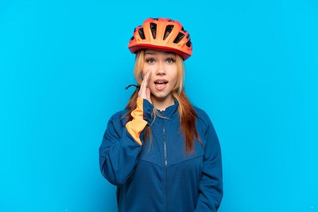 Garota jovem ciclista isolada em um fundo azul com expressão facial surpresa e chocada