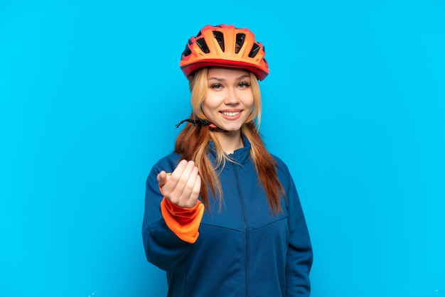 Garota jovem ciclista isolada em um fundo azul, convidando a vir com a mão. feliz que você veio