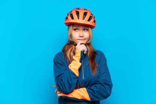 Garota jovem ciclista isolada em um fundo azul, tendo dúvidas e pensando