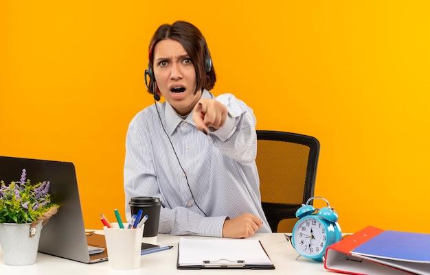 Garota jovem com raiva do call center usando fone de ouvido, sentada na mesa, apontando isolado na laranja