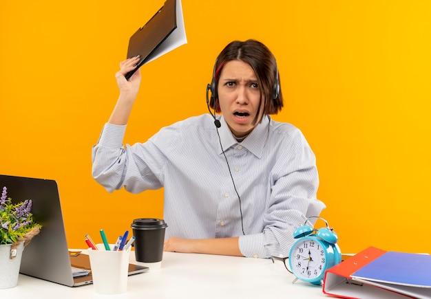 Garota jovem com raiva do call center usando fone de ouvido, sentada na mesa, levantando a área de transferência isolada em laranja