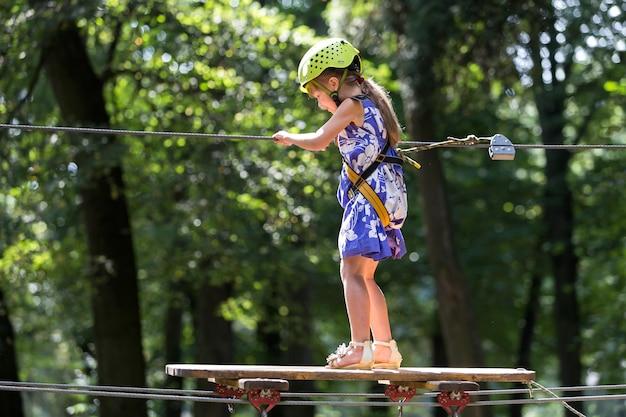 Garota jovem criança na maneira de corda no parque.