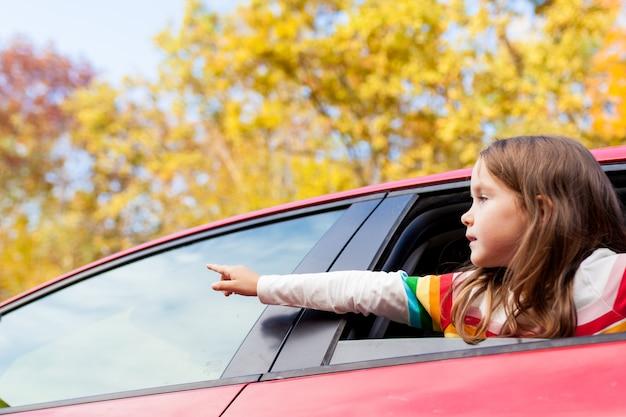 Garota jovem criança olhando pela janela do carro durante uma viagem em família para a natureza em um dia quente de outono