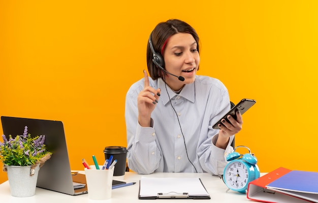 Garota jovem de call center impressionada usando fone de ouvido, sentada na mesa, segurando e olhando para o celular com o dedo levantado isolado em laranja