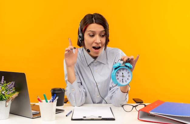 Garota jovem de call center impressionada usando fone de ouvido sentada na mesa, segurando e olhando para o despertador e levantando o dedo isolado em laranja