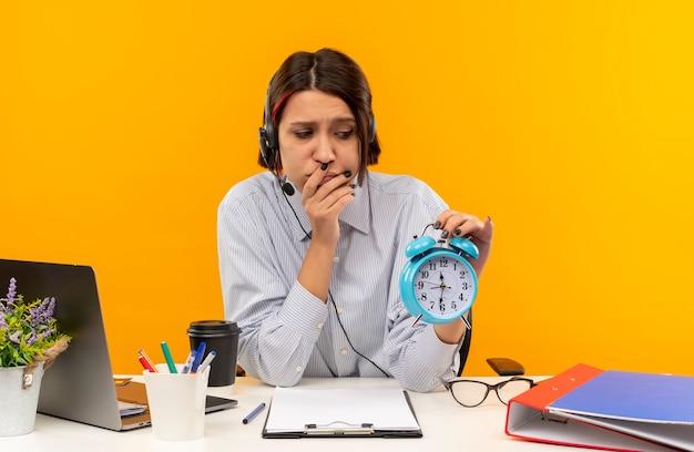 Garota jovem descontente de call center usando fone de ouvido, sentada na mesa com ferramentas de trabalho, colocando a mão na boca, segurando e olhando para o despertador isolado em um fundo laranja