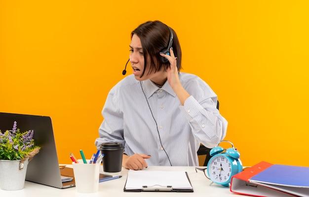 Garota jovem descontente do call center usando fone de ouvido, sentada na mesa com ferramentas de trabalho, olhando para laptop com a mão no fone de ouvido isolado em fundo laranja