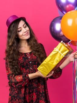 Garota jovem e animada com um chapéu de festa segurando balões e um pacote de presente, olhando para o pacote isolado na parede rosa
