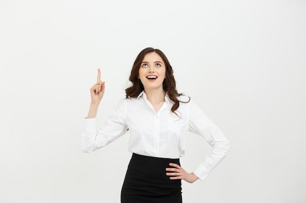 Garota jovem e atraente caucasiana abrir a boca e apontando o dedo indicador para o topo.