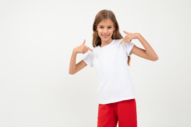 Garota jovem e atraente caucasiana em uma camiseta branca com um layout e calça vermelha em branco