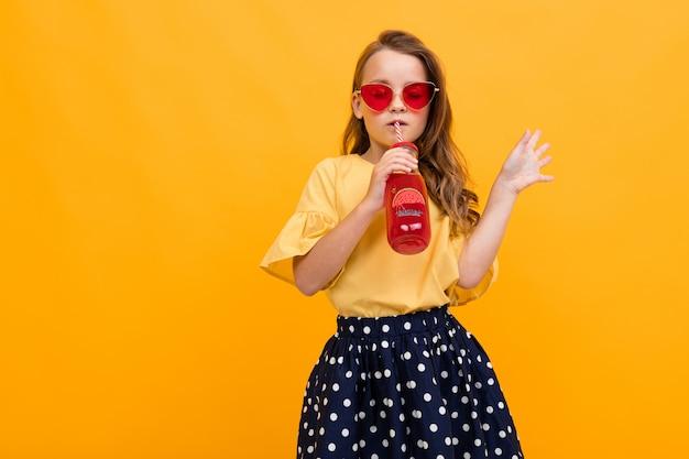 Garota jovem e atraente caucasiana em uma saia e uma camiseta com um copo de suco de melancia posando no estúdio amarelo com espaço de cópia