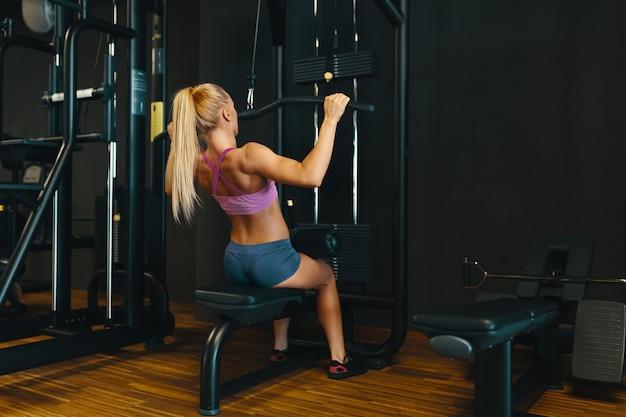 Garota jovem e atraente caucasiana no desgaste do esporte malhando braços um