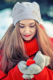 Garota jovem e atraente com cabelo comprido em um casaco vermelho e lenço com o presente em uma caixa em forma de um coração nas mãos.