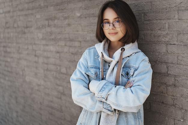 Garota jovem e atraente com cabelo curto, usando óculos e roupas de estilo urbano, encostada em uma parede de tijolos.