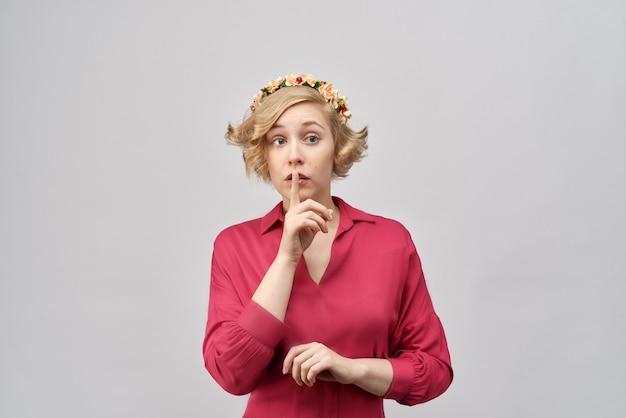 Garota jovem e atraente com cabelo loiro curto encaracolado em um vestido vermelho clássico com coroa de flores na cabeça, coloca um dedo nos lábios e pedindo para ficar quieto ou secreto.